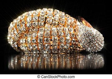 Shiny Gold Bracelet and Ring on Black Background - A shiny...