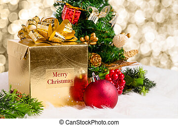 Shiny gold gift box with Merry Christmas word with red decoration ball, pine code and xmas tree on white fur with sparkle god light bokeh background, Winter Holiday seasonal greeting card