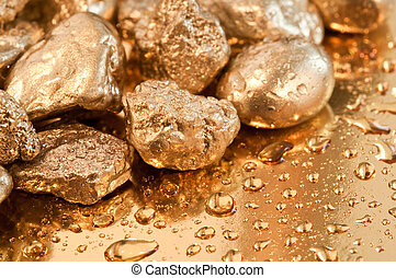 shiny gold nuggets and water drop background. closeup.