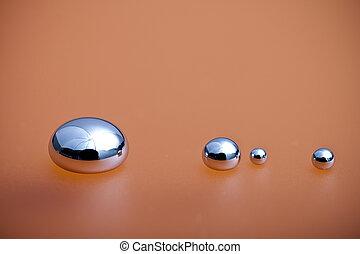 Shiny Mercury drops on a orange background