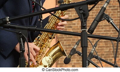 shiny saxophone in the hands of a musician at a concert