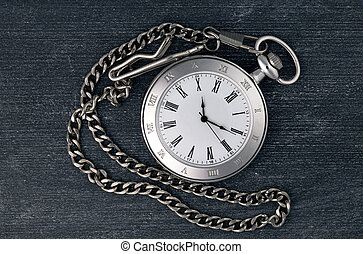 Shiny silver chain watch on a black chalkboard background