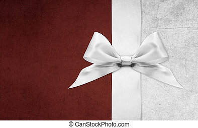 Shiny silver satin ribbon bow on red background