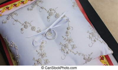 Shiny silver wedding rings on satin pillow close up - silver...
