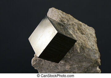 Shiny smooth regular shape pyrite cube on a dark background...