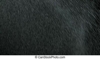 Shiny splashes of water fly on a black background. Slow motion. Spraying liquid in the air. Microdroplets of water fly. Aerosols. Close up. Particles create texture for your design