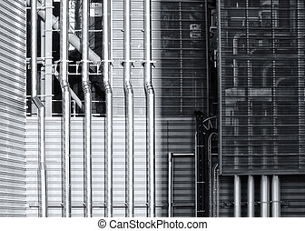 shiny steel pipes running down a metal industrial building