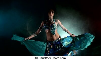 Shiny torso of a beautiful young girl belly dancer on a black, blue, smoke, back light