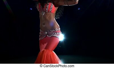 Shiny torso of a beautiful young girl belly dancer on a black, back light