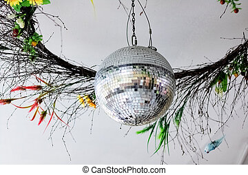 Shiny white disco ball on ceiling closeup