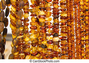 Shiny womanly amber necklaces on stall at the bazaar