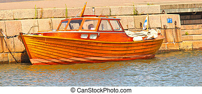 Shiny wooden boat, mooring in water at harbor