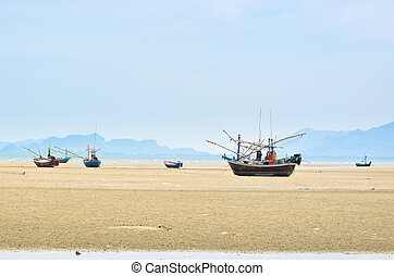 Ship aground on the beach - Many small fishing wooden boats...