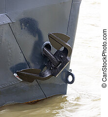 Ship anchor in the nasal cleft. The blades of the ship's anchor in black on a gray background of the bow of a watercraft. The nose of a transport barge on a background of dirty river water.