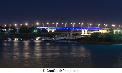 Ship and illuminated bridge on the riverside Ural in city Atyrau timelapse hyperlapse. Aerial view from a bridge. Kazakhstan