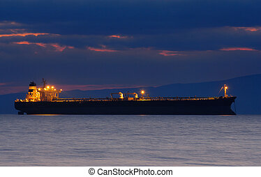 Image of an illuminated merchant ship at dusk