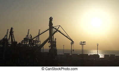 Ship crane seaport - Morning. The first rays of sunshine...