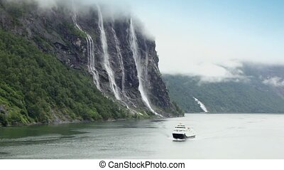 Ship floats by fiord near Seven Sisters waterfall on mountain