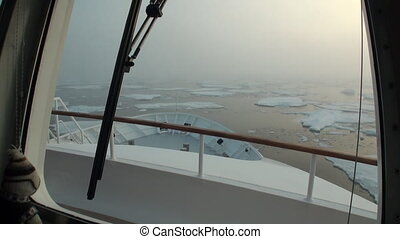 Ship floats in the Arctic Ocean on background of ice of Greenland.