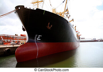 A large red and black tanker ship being renovated in a shipyard