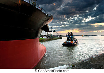 Ship in the harbor - Tug boat taking out the ship from the...