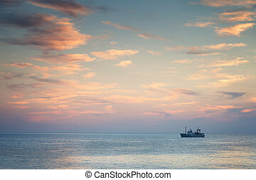 Ship in the sea at sunset
