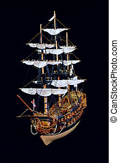 Ship model - The model of the sailing ship is against a dark...