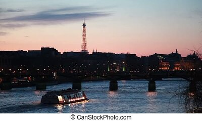 Ship moves on river to iron bridge of night in Paris