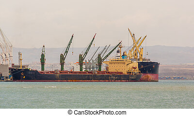 A Large ship anchored on Djibouti port with giant cranes unloading its cargo