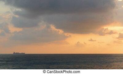 ship on horizon of sea at sunset - timelapse