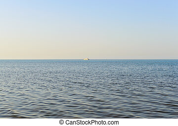 Ship on the horizon of the sea evening