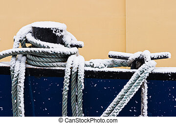 Ship ropes covered with snow in winter