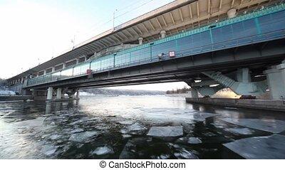 Ship sail in icy river under Luzhnetsky metro bridge at...