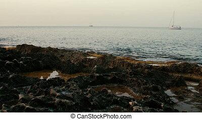 Ship sailing along the rocky coast of Mediterranean Sea.