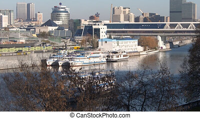Ship sailing by river along city embankment view