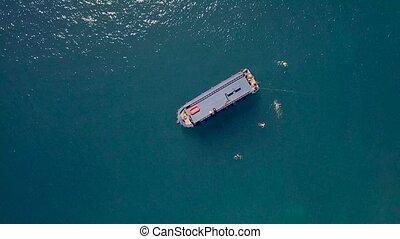 Ship sailing in blue sea and people swimming in water aerial view. Drone flying over sailing boat in sea and people bathing in blue water.