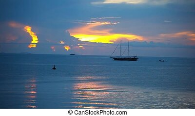 Ship sails on a background of beautiful sunset