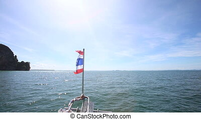 ship with flag in ocean past islands - ship with developing...