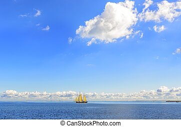 Ship with sails in the sea on the horizon.