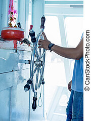 Selected focus shipmaster working on hand control on helm