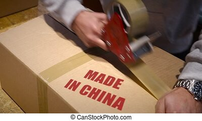 Shipment of goods made in china - Production worker sealing...