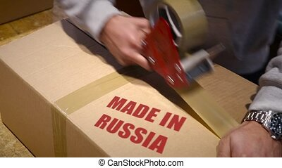 Shipment of goods made in Russia - Production worker sealing...