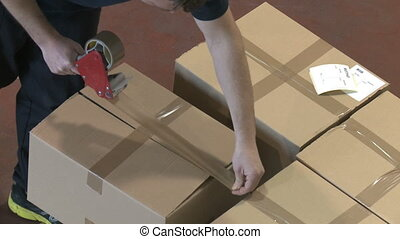 Shipping boxes - Top view of an employee closes cardboard...