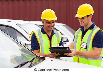 shipping  company workers checking vehicles report