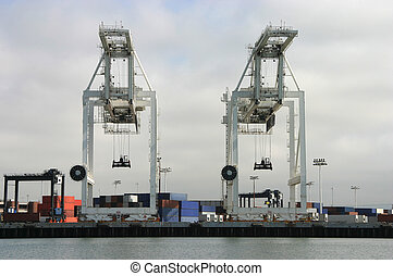 Shipping Cranes - Two large cargo cranes are poised to...