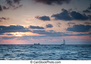 Ships at sea against the sky with clouds at sunset