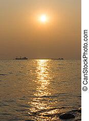ships at sea on the horizon at sunset