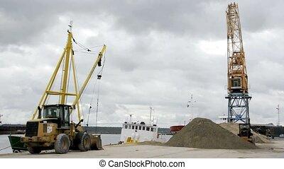Ship\'s dredge unloads sand on dock
