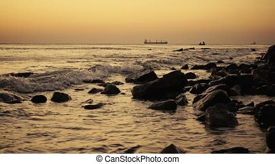 Ships in the sea and fishermen in a boat at sunset slow mo -...