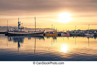 Ships lying in the harbor of Husavik at sunset, Iceland